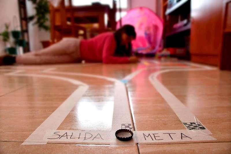 Una niña prepara una pista para una carrera de chapas este domingo durante el confinamiento. EFE