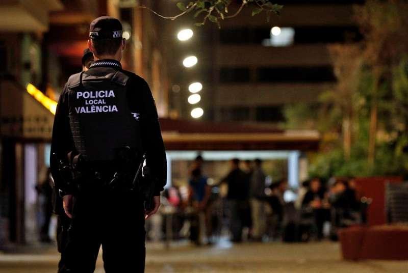 Agentes de la Policía Local vigilan que se cumpla la normativa del cierre de los locales en una conocida zona de ocio de València. EFE