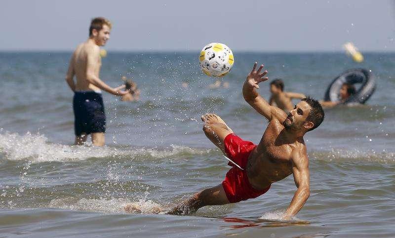Unos jóvenes disfrutan del buen tiempo en una playa de Valencia. EFE/Archivo