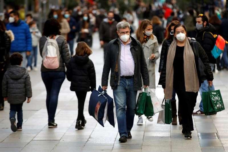 Un grupo de personas con mascarilla camina por la calle. EFE