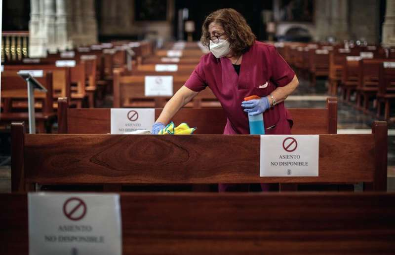 Imagen de archivo de una mujer desinfectando los bancos de la Catedral de València. EFE