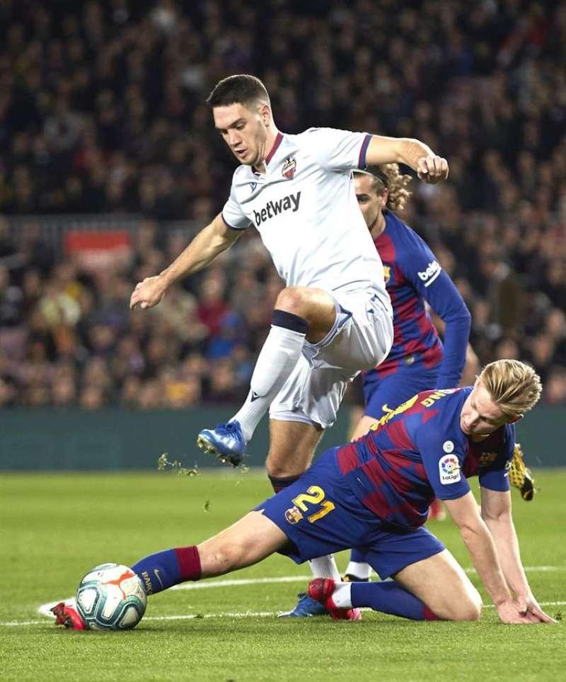 El centrocampista del FC Barcelona Frenkie De Jong (d) pelea un balón con Nikola Vukcevic, del Levante. EFE/Alrchivo