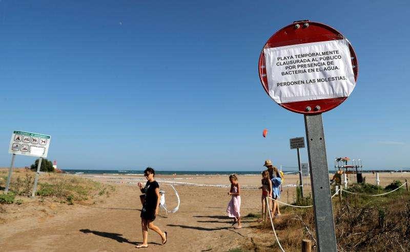 Varios bañistas pasan junto a la señal que informa de la prohibición en la paya de La Pobla de Farnals (Valencia). EFE/Archivo