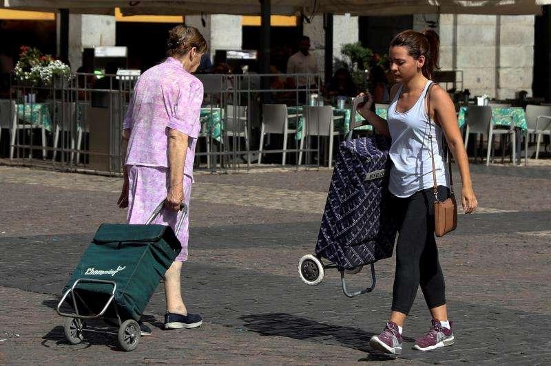 Dos personas acuden al mercado con con sus carros de la compra. EFE/Archivo