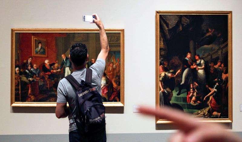 Un joven toma una fotografía de uno de los cuadros del pintor alicantino Vicente Rodes Aries, en una exposición en el Museo de Bellas Artes de Valencia. EFE/Archivo