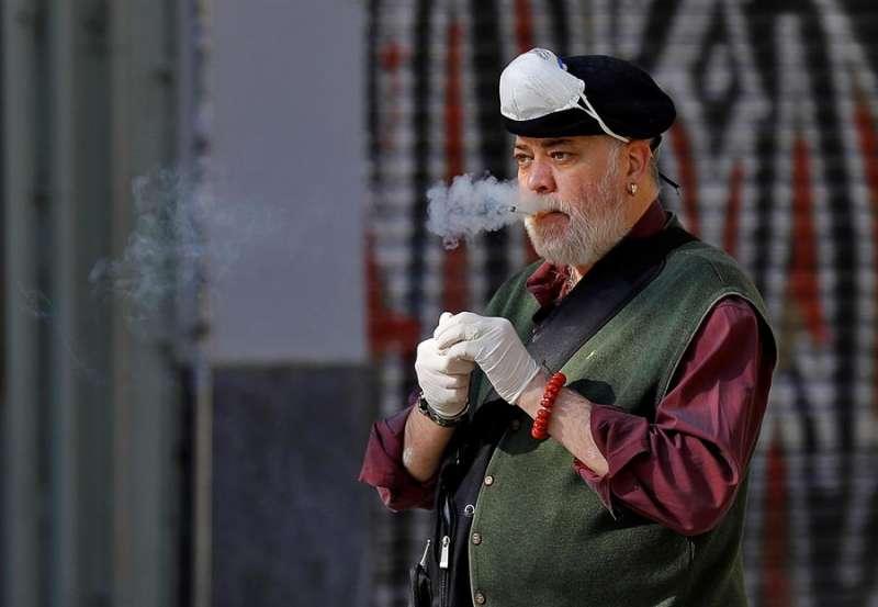 Un hombre se retira por un momento su mascarilla de protección para fumar un cigarrillo a las puertas del Mercado Central de València. EFE/Manuel Bruque/Archivo
