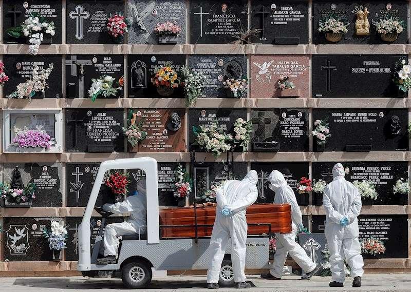 Personal del cementerio del Cabañal transporta un féretro durante un entierro al que han podido asistir tres familiares. EFE