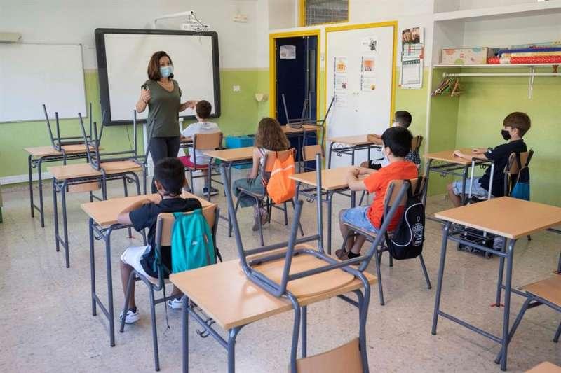 Una maestra imparte clase en un colegio con niños guardando la distancia de seguridad. EFE