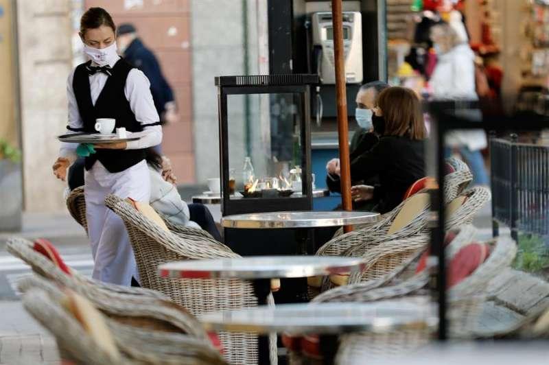 Una camarera atiende una terraza en Valencia. EFE/ Juan Carlos Cárdenas/Archivo