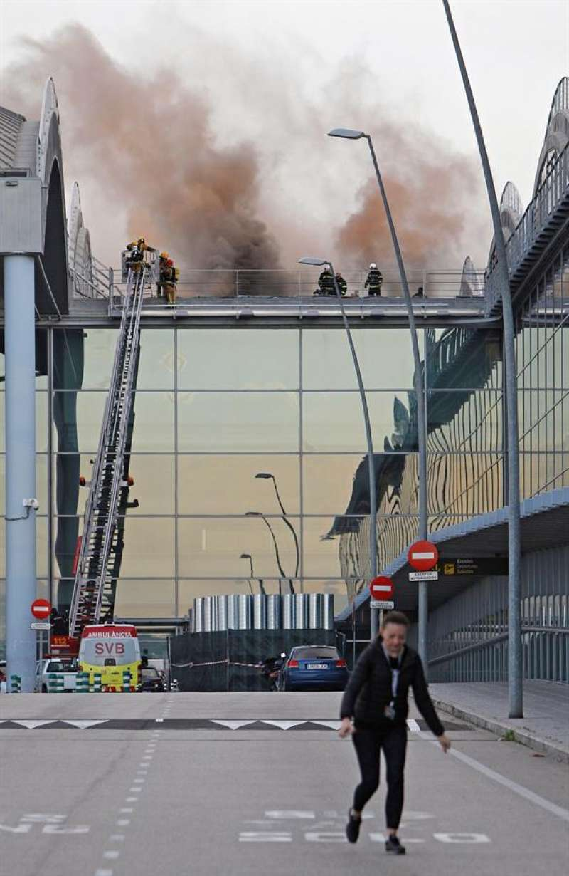Un equipo de bomberos accede al techo del aeropuerto de Alicante-Elche para atajar el incendio. EFE/Morell