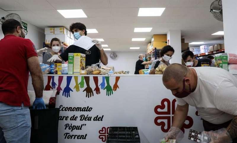 Varios voluntarios del economato interparroquial gestionado por Cáritas en la ciudad de Torrent (Valencia). EFE