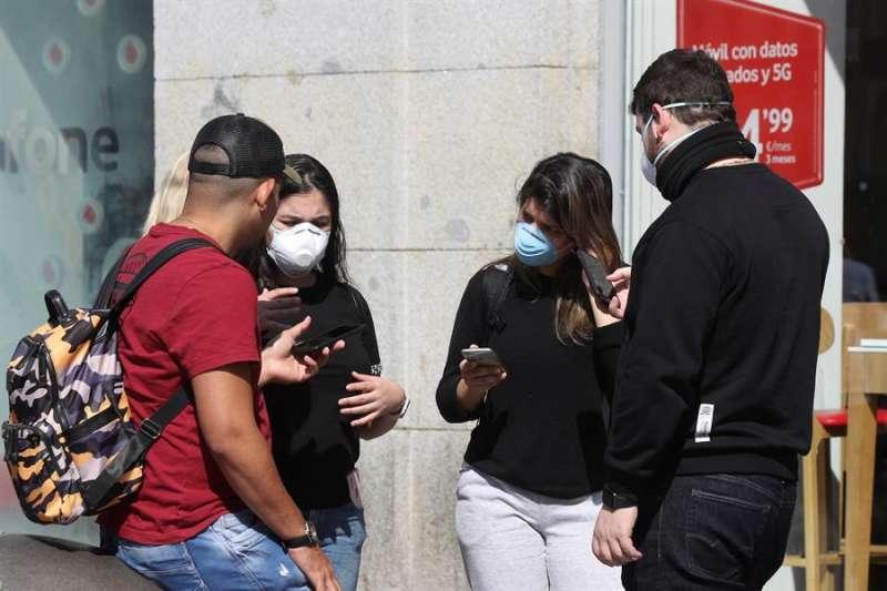Varios jóvenes con mascarilla consultan sus teléfonos móviles. EFE/Archivo