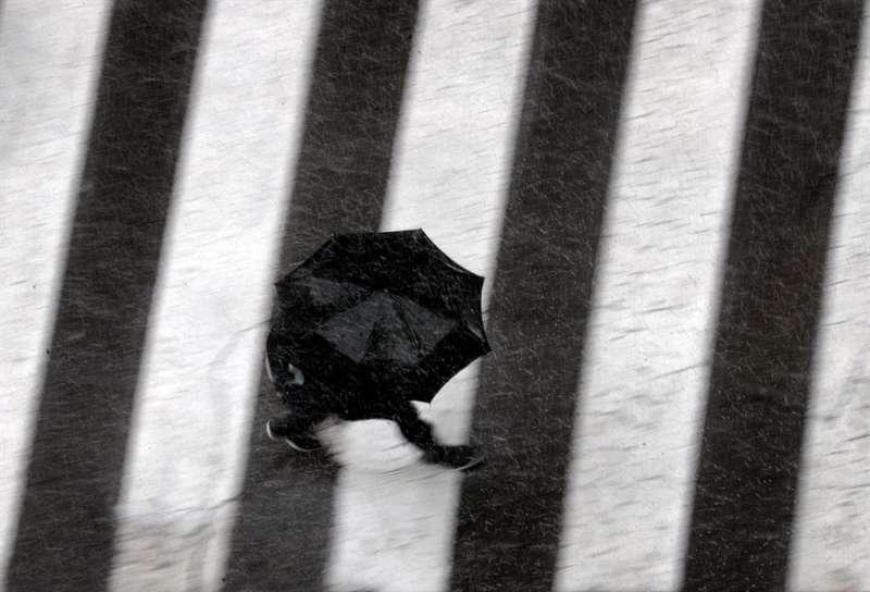 Una persona se protege con un paraguas de lluvia. EFE/Kai Försterling/Archivo