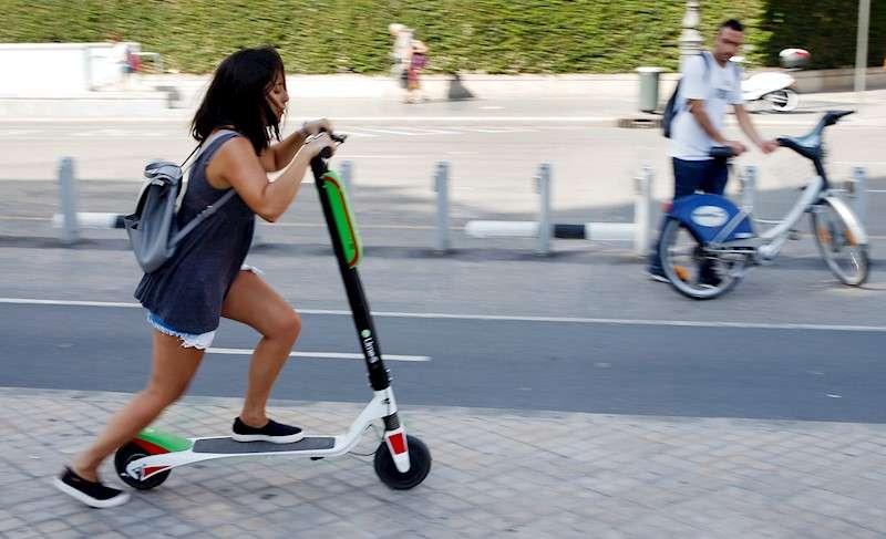 Una joven circula en patinete por una acera de Val�ncia. EFE