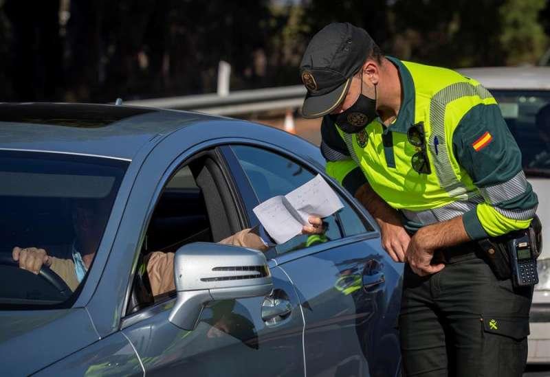 Un agente de la Guardia Civil de Tráfico comprueba un documento aportado por un conductor durante un control. EFE