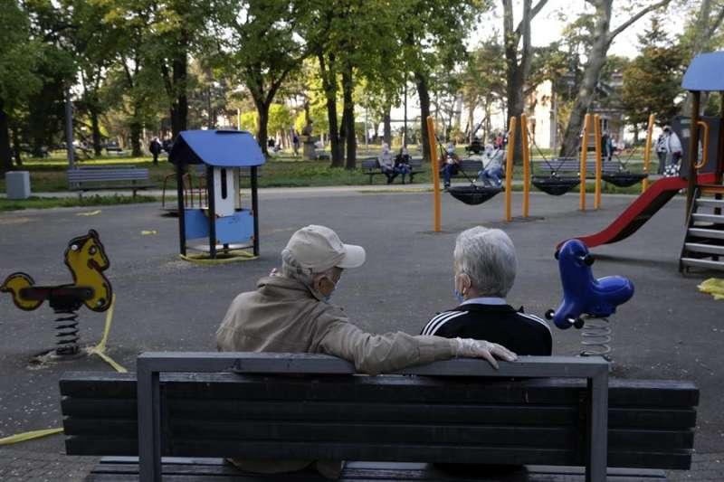Una pareja de ancianos sentados en un parque infantil desierto. EFE/Archivo