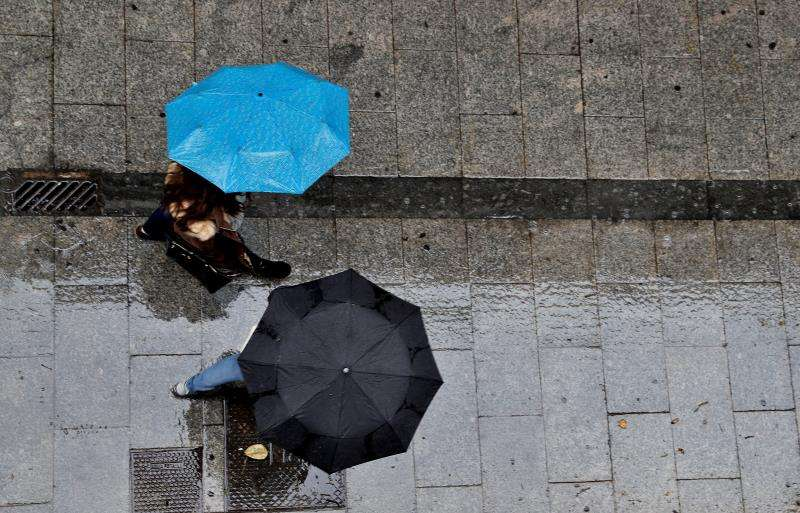 Dos personas se protegen con paraguas de la lluvia. EFE/Archivo