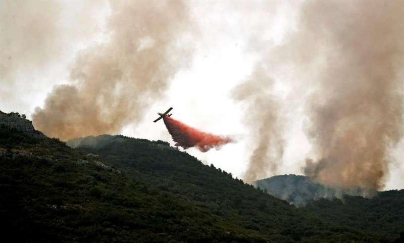 Una avioneta lanza agua con retardantes sobre el frente de un incendio. EFE