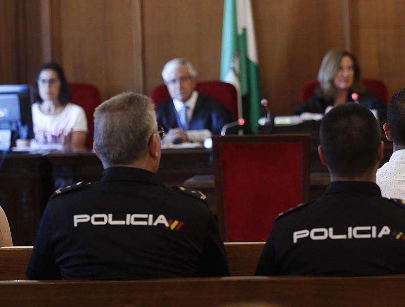Policías custodian a una persona durante un juicio. EFE/Archivo