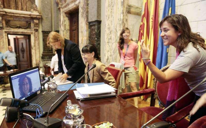 La concejal de Igualdad en el Ayuntamiento de València, Isabel Lozano (d), cruza los dedos mientras habla por videoconferencia con la concejala Neus Fábregas (en pantalla) al inicio de un pleno. EFE/Archivo