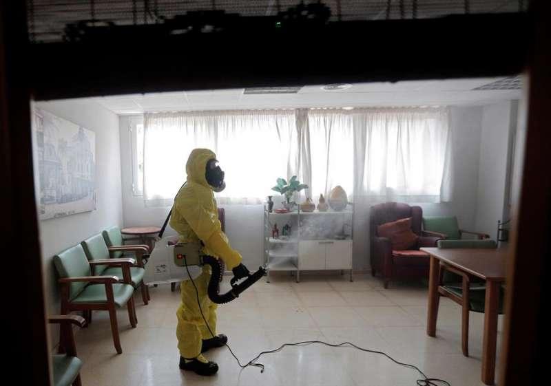 Un miembro de la UME realiza labores de desinfección, como medida de prevención, en una residencia de ancianos libre de casos de Covid-19. EFE