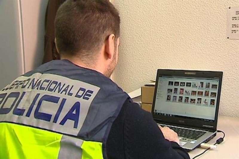 Un agente de la Policía Nacional revisa material de un ordenador durante una operación. EFE/Archivo
