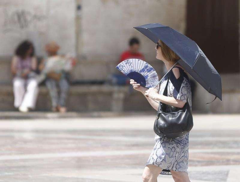 Una mujer se abanica y se protege del sol con un paraguas en Valencia.EFE/Archivo
