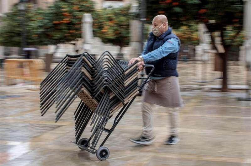 Un trabajador de un restaurante del centro de València recoge la terraza. EFE
