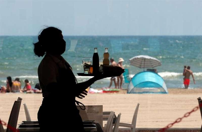 Una camarera lleva una bandeja con bebidas en un restaurante de la playa. EFE