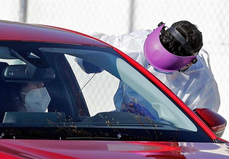 Personal sanitario realiza pruebas PCR en el interior de los vehículos. EFE