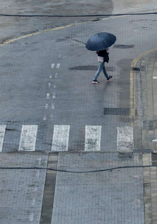 Una persona se protege con un paraguas de la lluvia mientras cruza una calle desierta durante el 15 de abril. EFE/ Ana Escobar / Archivo