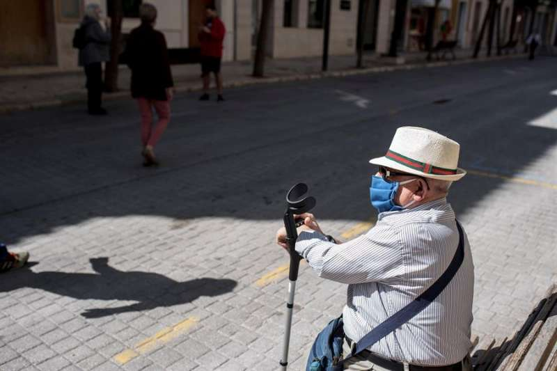 Una persona mayor en un banco con mascarilla. EFE