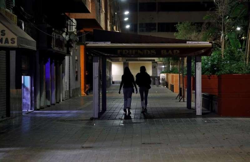 Dos jóvenes regresan a su casa, en una conocida zona de ocio de València, poco antes de la entrada en vigor del toque de queda. EFE