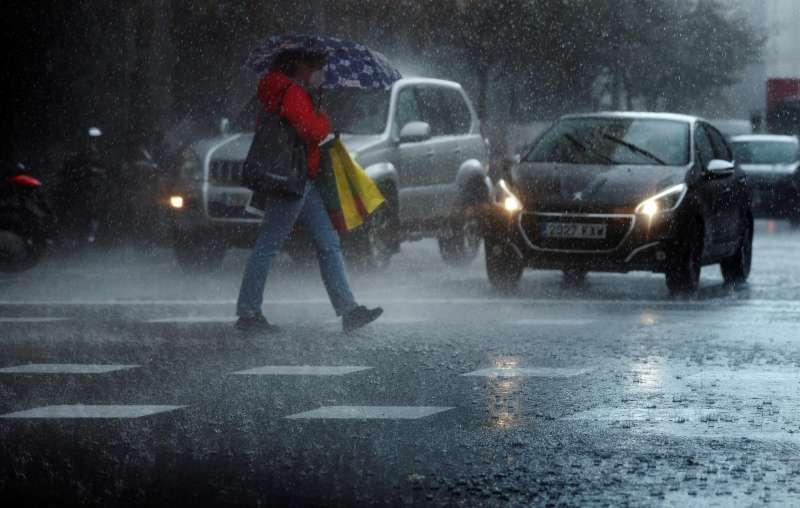 Una persona camina bajo una intensa lluvia. EFE/Kai Försterling/Archivo