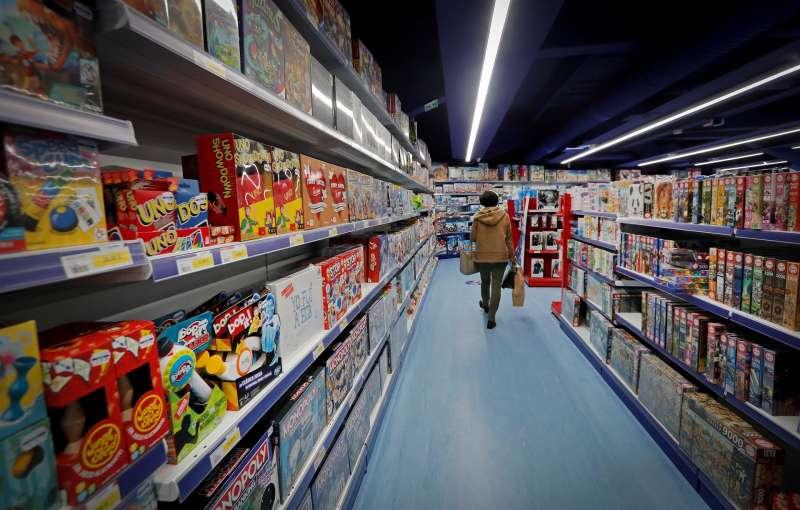 Una mujer camina por el pasillo de los juegos de mesa en un comercio de juguetes.