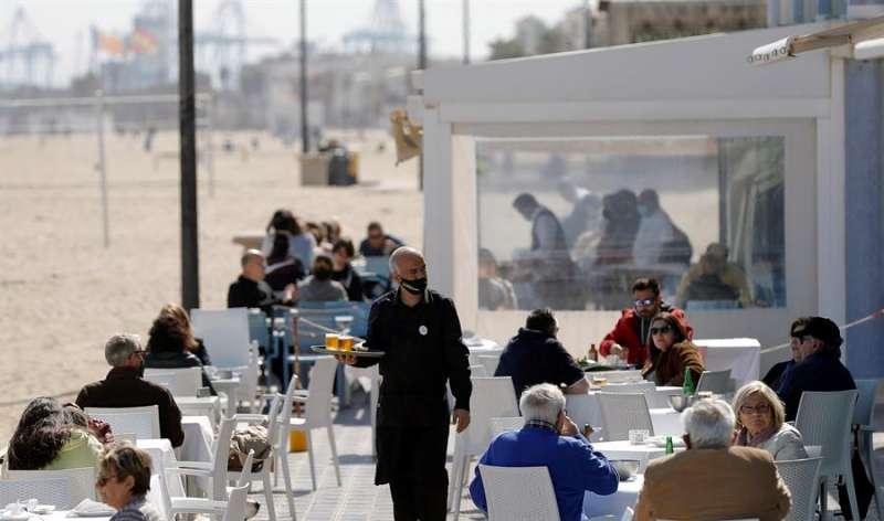 Un camarero atiende las mesas de una terraza en uno de los restaurantes de la playa de la Malvarrosa de Valencia