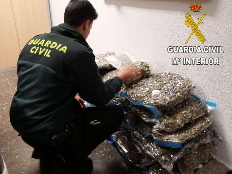 Un agente de la Guardia Civil junto a la droga incautada