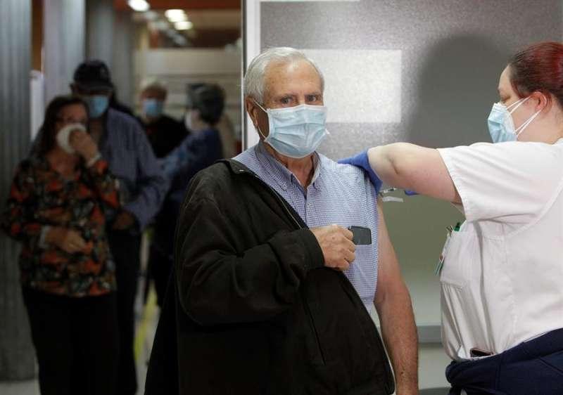 Personal sanitario vacuna a una de las personas de 78-79 años de edad
