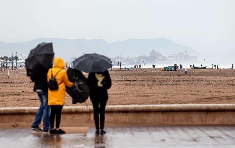 Varias personas observan la playa de Las Arenas de Valencia afectada por el temporal de este fin de semana. EFE