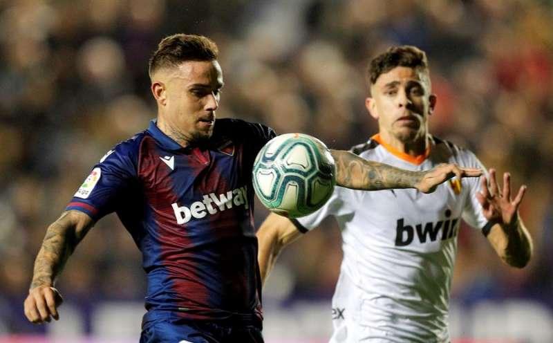 El delantero del Levante Roger Martí (i) protege un balón ante Paulista, del Valencia. EFE/Kai Försterling