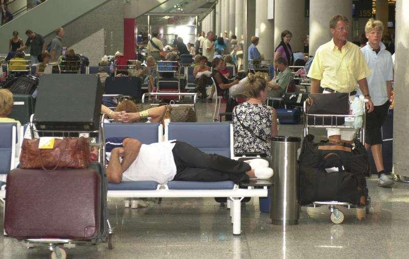 Pasajeros descansan en una terminal por la cancelación y retrasos de vuelos. EFE/Archivo