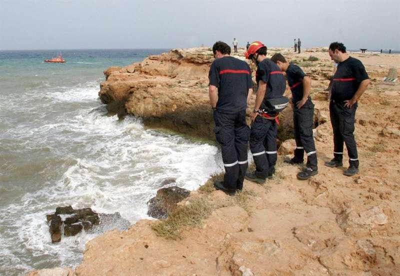 Bomberos observan el lugar, con fuerte oleaje, donde se ahogó un bañista. - EFE