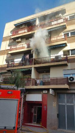 Los bomberos trabajan en las labores de extinción en la vivienda incendiada. EPDA