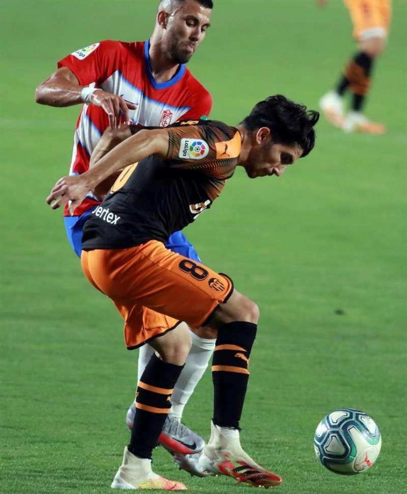 El centrocampista del Valencia, Carlos Soler (d), disputa el balón con el jugador del Granada, Fede Vico. EFE / Archivo