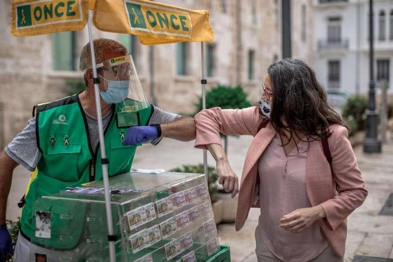 La vicepresidenta del Consell y consellera de Igualdad y Políticas Inclusivas, Mónica Oltra, saluda a un vendedor de cupones de la ONCE. EFE