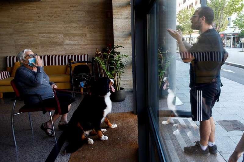 Una persona visita a un familiar interno en una residencia y conversa con él a través de un cristal. EFE