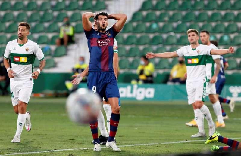 El delantero del Huesca Rafa Mir (c) se lamenta tras una ocasión fallada ante el Elche en el partido de LaLiga disputado en el estadio Martínez Valero. EFE