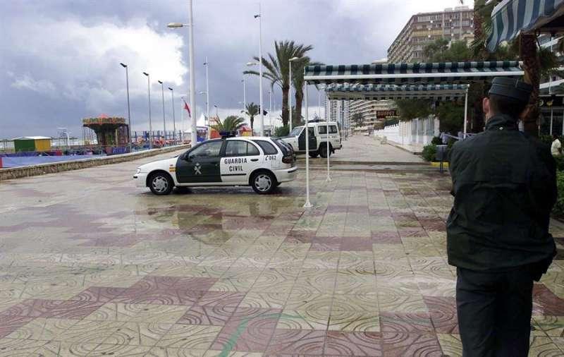 Un agente de la Guardia Civil y varias patrullas en el municipio de Cullera. EFE