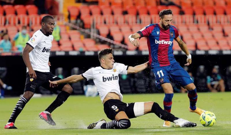 El delantero del Levante UD José Luis Morales (d), perseguido por el brasileño Gabriel Paulista (c), del Valencia CF, dispara a puerta para conseguir su gol, primero del equipo ante el Valencia, en el partido de la primera jornada de Liga en Primera División que se disputó en el estadio de Mestalla. EFE/ Juan Crlos Cárdenas