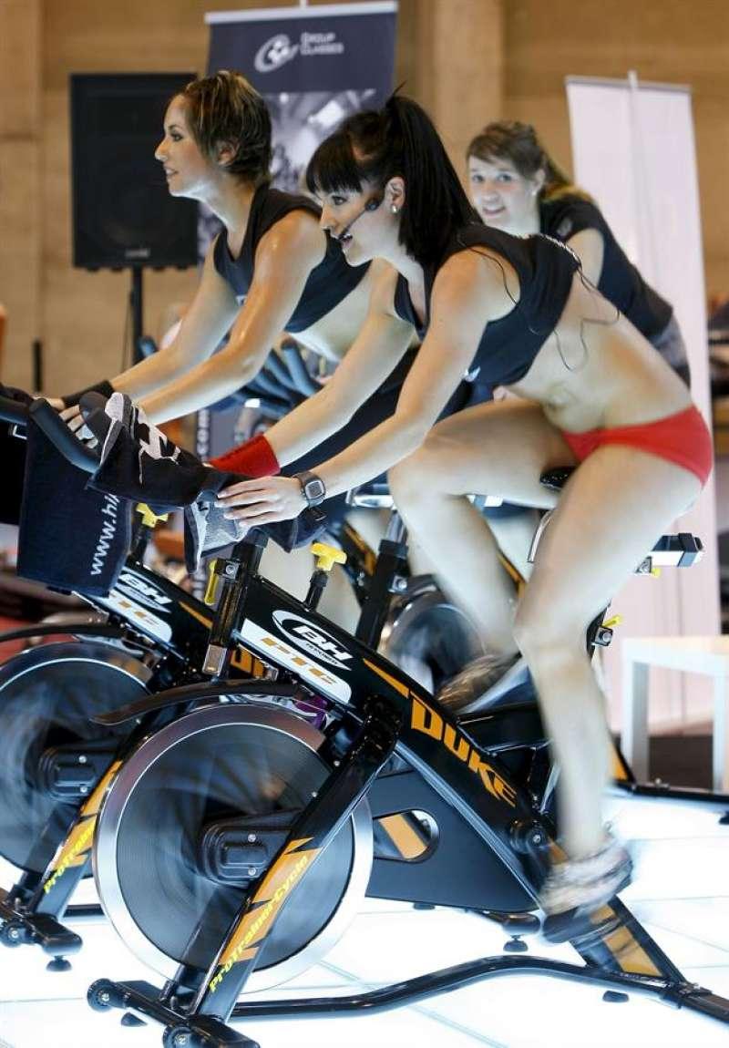 Tres mujeres hacen deporte sobre bicicletas estáticas. EFE/Archivo